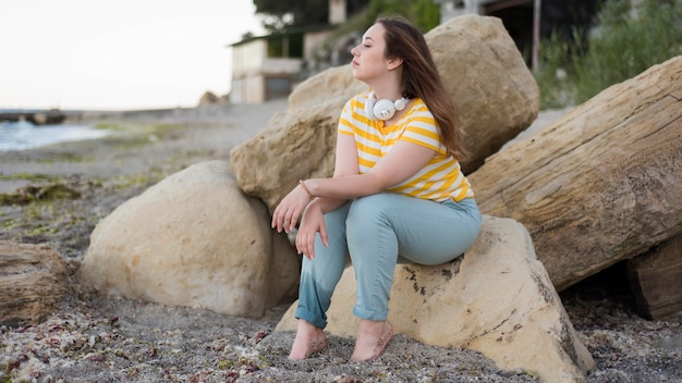 Pełne ujęcie kobiety siedzącej na skałach na plaży