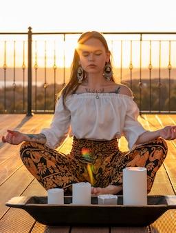 Pełne ujęcie kobiety siedzącej o zachodzie słońca