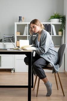 Pełne ujęcie kobiety siedzącej przy biurku