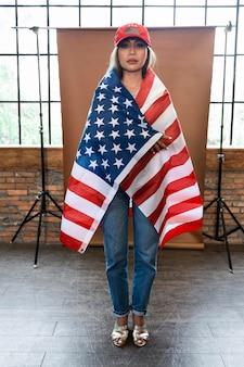 Pełne ujęcie kobiety trzymającej amerykańską flagę