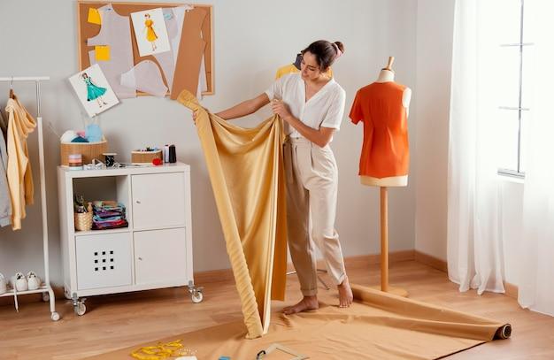 Pełne ujęcie kobiety trzymającej tkaninę