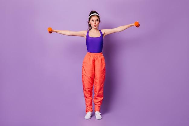 Pełne ujęcie kobiety w szerokich spodniach i czapce, wykonującej ćwiczenia na dłonie z hantlami na liliowej ścianie