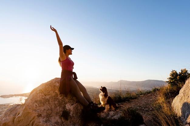 Pełne ujęcie kobiety z psem w przyrodzie