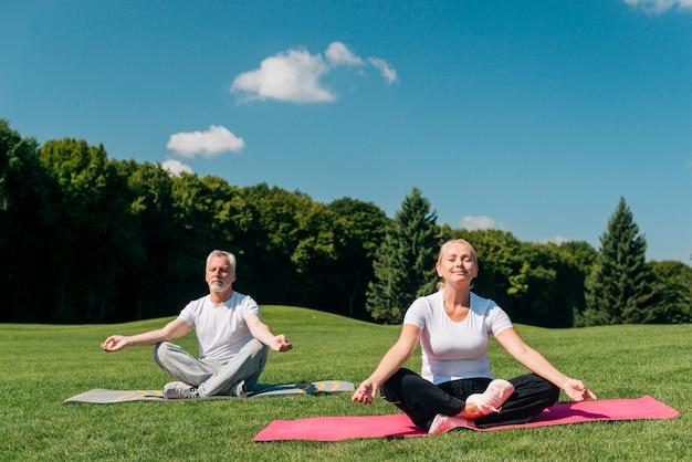 Pełne ujęcie ludzi medytujących na zewnątrz