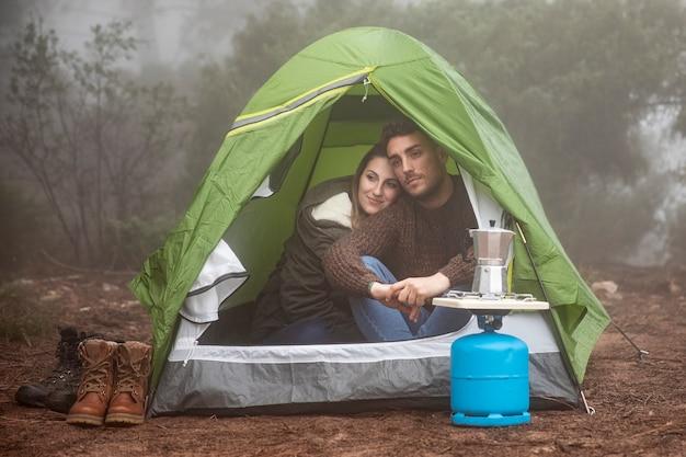 Pełne ujęcie ludzi siedzących w namiocie