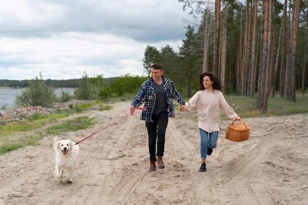 Pełne ujęcie ludzi spacerujących z psem na plaży?