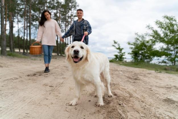 Pełne ujęcie ludzi spacerujących z psem na zewnątrz