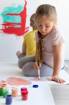 Pełne ujęcie malowania dziewczynki pędzlem