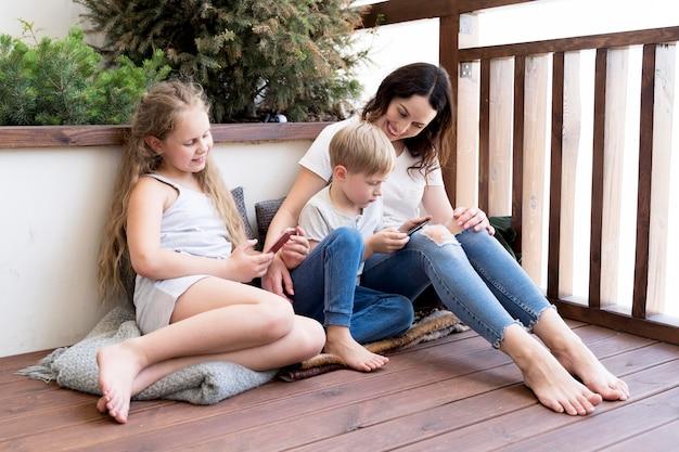 Pełne ujęcie matki i dzieci na podłodze