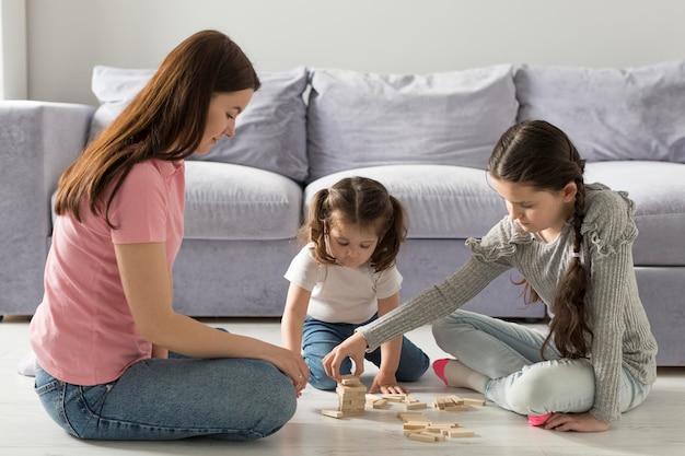 Pełne ujęcie matki i dziewcząt na podłodze