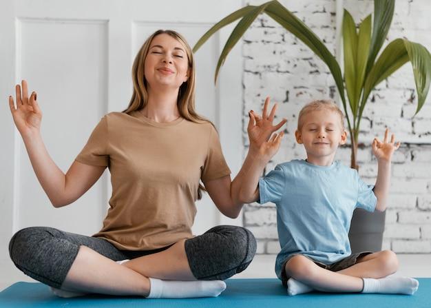 Pełne ujęcie medytujące dziecko i kobieta
