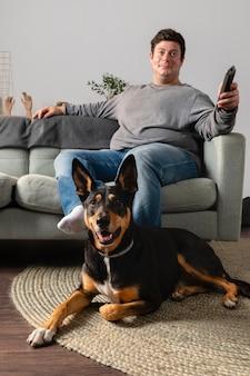 Pełne ujęcie mężczyzny i psa w pomieszczeniu