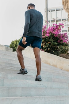 Pełne ujęcie mężczyzny idącego po schodach