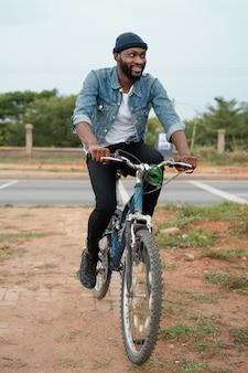 Pełne ujęcie mężczyzny jadącego na rowerze