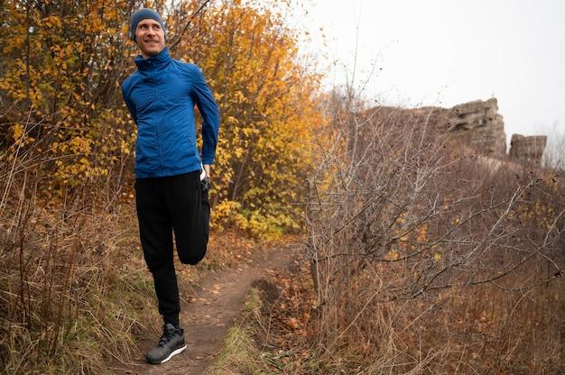 Pełne ujęcie mężczyzny prostującego nogi w lesie