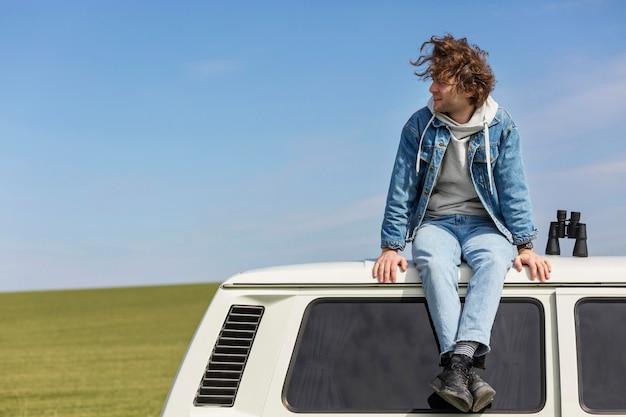 Pełne ujęcie mężczyzny siedzącego na furgonetce