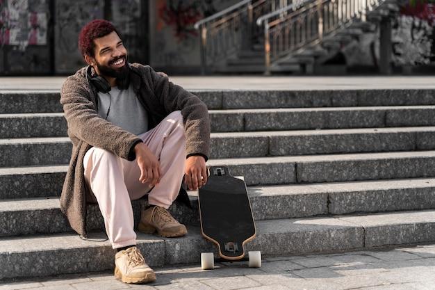 Pełne ujęcie mężczyzny siedzącego na schodach