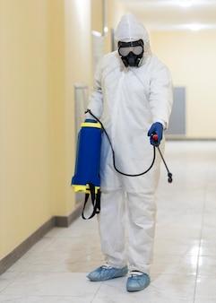 Pełne ujęcie mężczyzny trzymającego zbiornik środka dezynfekującego