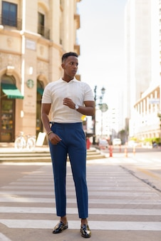 Pełne ujęcie młodego afrykańskiego biznesmena na zewnątrz przechodzącego przez przejście dla pieszych
