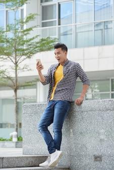 Pełne ujęcie młodego przystojnego faceta podekscytowanego wiadomościami odczytanymi w smartfonie