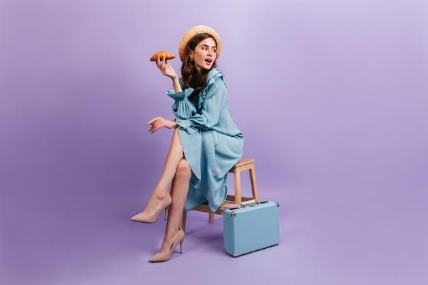 Pełne ujęcie młodej damy w eleganckiej niebieskiej sukience. kobieta siedzi na stołku obok walizki i trzyma pysznego rogalika.