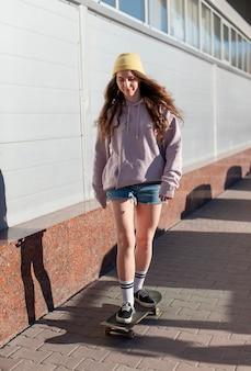Pełne ujęcie młodej dziewczyny na łyżwach na zewnątrz