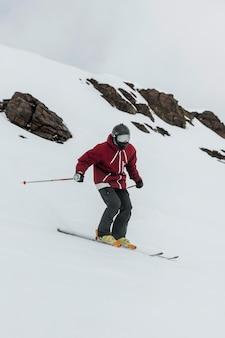 Pełne ujęcie narciarza trzymającego kijki narciarskie