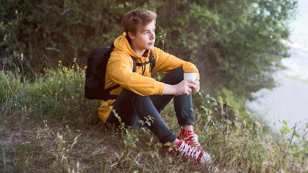 Pełne ujęcie nastolatka siedzącego na ziemi w lesie