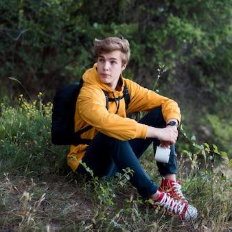 Pełne ujęcie nastolatka z plecakiem siedzi na ziemi w lesie