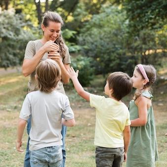 Pełne ujęcie nauczyciela i dzieci na świeżym powietrzu