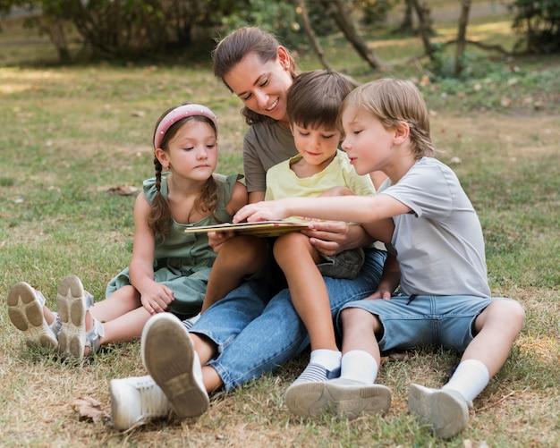 Pełne ujęcie nauczyciela i dzieci siedzących na ziemi