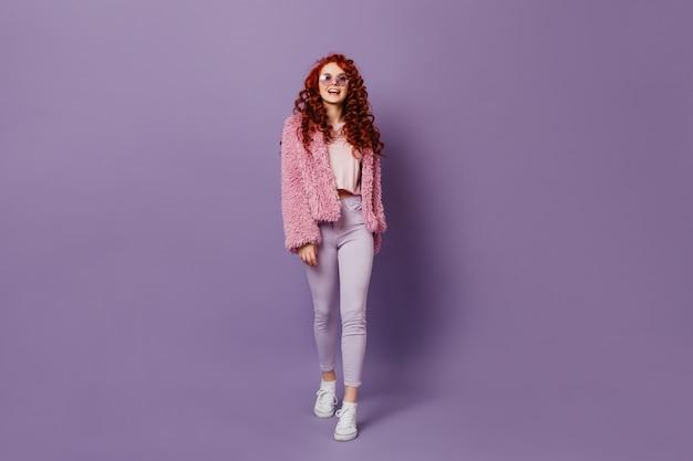 Pełne ujęcie niegrzecznej rudowłosej dziewczyny w okrągłych okularach, białych dżinsach i różowym płaszczu na fioletowej przestrzeni.