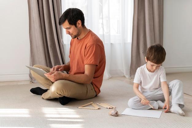 Pełne ujęcie ojca i dzieciaka na podłodze