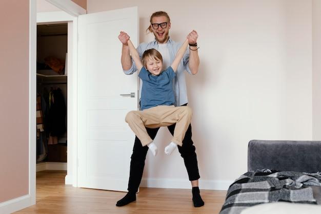 Pełne ujęcie ojca trzymającego dziecko