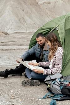 Pełne ujęcie osób z mapą na piasku