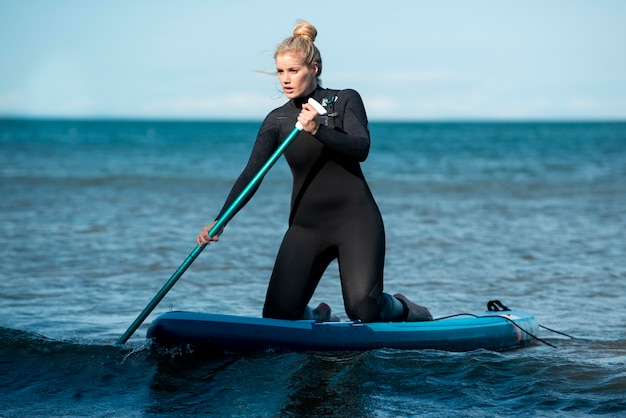 Pełne ujęcie ostrożna kobieta paddleboarding