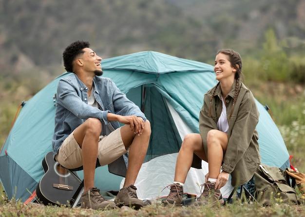 Pełne ujęcie para siedzi w pobliżu namiotu