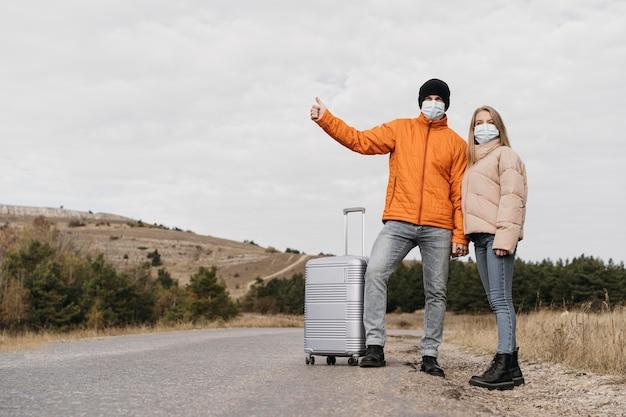Pełne ujęcie pary autostopowej z maskami