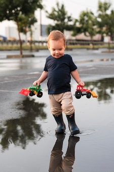 Pełne ujęcie pięknego dzieciaka bawiącego się na zewnątrz