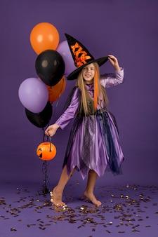 Pełne ujęcie pięknej dziewczyny w stroju czarownicy