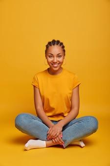 Pełne ujęcie pozytywnej, beztroskiej kobiety siedzi ze skrzyżowanymi nogami, uśmiecha się delikatnie, ubrana niedbale, cieszy się domową atmosferą, odizolowane na żółtej ścianie pustej przestrzeni powyżej. ludzie, styl życia