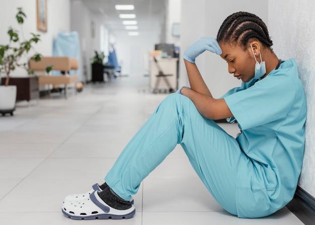 Pełne ujęcie pracownika służby zdrowia siedzącego na podłodze