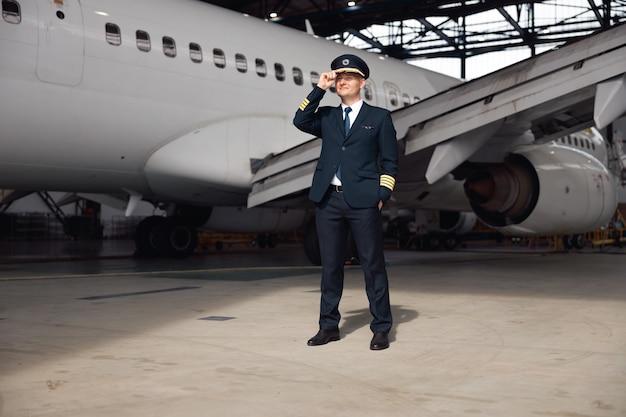 Pełne ujęcie przedstawiające pewnego pilota w mundurze, odwracającego wzrok, poprawiającego kapelusz, stojącego przed dużym samolotem pasażerskim w hangarze na lotnisku. samolot, zawód, koncepcja transportu
