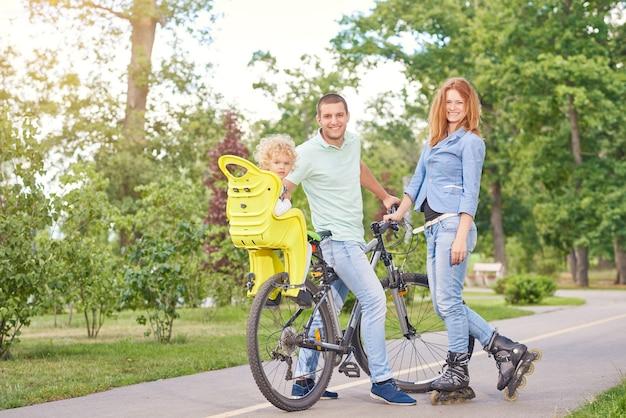 Pełne ujęcie przedstawiające szczęśliwą młodą rodzinę, która razem jeździ na rowerze i rolkach w miejscowym parku.