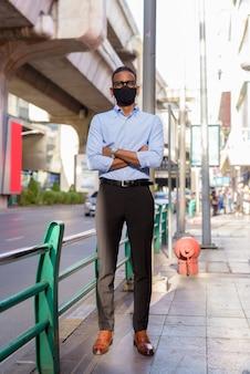 Pełne ujęcie przystojnego czarnego afrykańskiego biznesmena na zewnątrz w mieście latem, noszącego maskę na twarz w celu ochrony przed wirusem koronowym