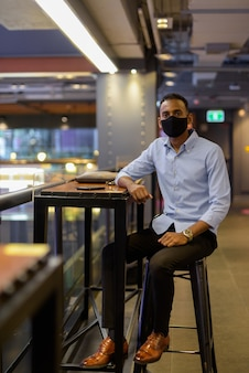 Pełne ujęcie przystojnego czarnego afrykańskiego biznesmena siedzącego w centrum handlowym podczas noszenia maski na twarz, aby chronić przed pionowym ujęciem covid-19