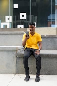 Pełne ujęcie przystojnego czarnego afrykańskiego mężczyzny noszącego żółtą koszulkę na zewnątrz w mieście podczas korzystania z telefonu komórkowego