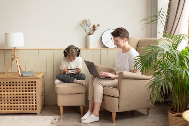 Pełne ujęcie rodzica i dziecka z urządzeniami