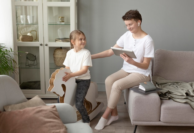 Pełne ujęcie rodzica z tabletem w domu