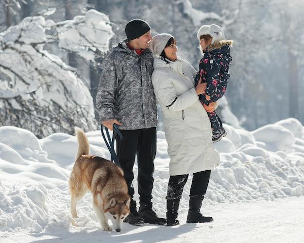 Pełne ujęcie rodziny z psem na zewnątrz